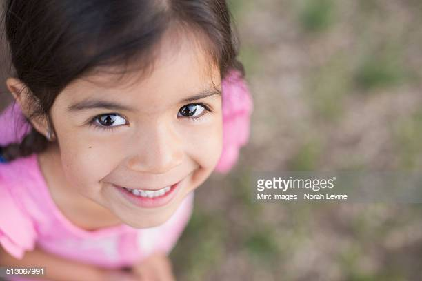 View from above of a child, a girl with dark brown hair and brown eyes.
