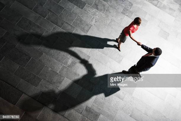 view from above of a handshake and shadows between a businessman and business woman. - suspicion stock pictures, royalty-free photos & images