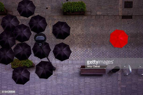 View from above of a man with red umbrella stands out from the rest of black umbrellas in a rainy and dark day in the city.