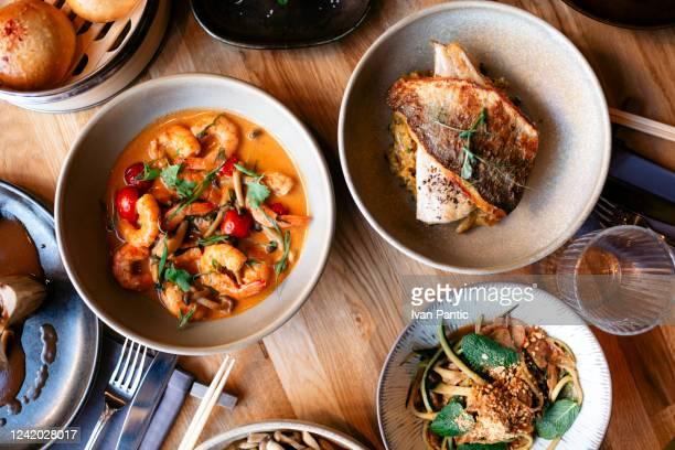 東南アジア、典型的なアジア料理のミックスの上からの眺め - ダイニングテーブル ストックフォトと画像