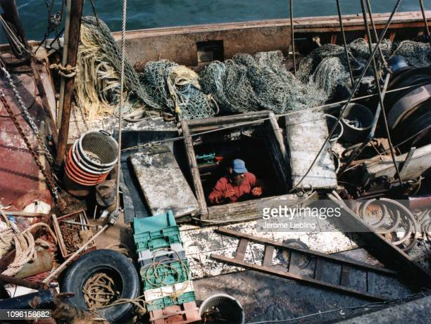 View from above of an unidentified fisherman as he climbs through the hatch from the cargo hold onto the deck of a fishing boat laden with nets and...