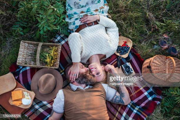 view from above of happy mature couple lying outdoors in autumn nature, having picnic. - picknick stock-fotos und bilder