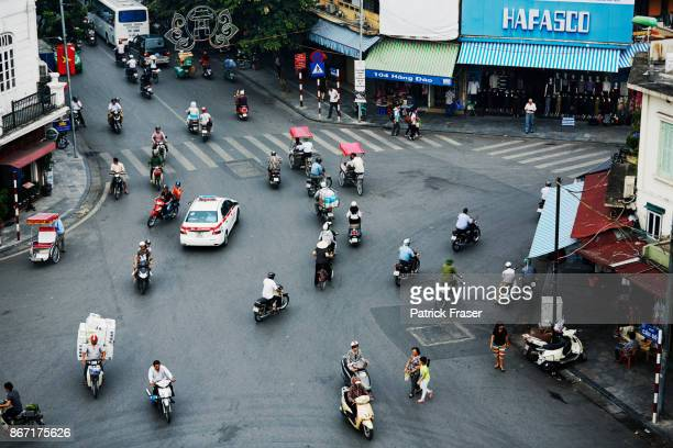 View from above of moped commuters on busy street in Hanoi