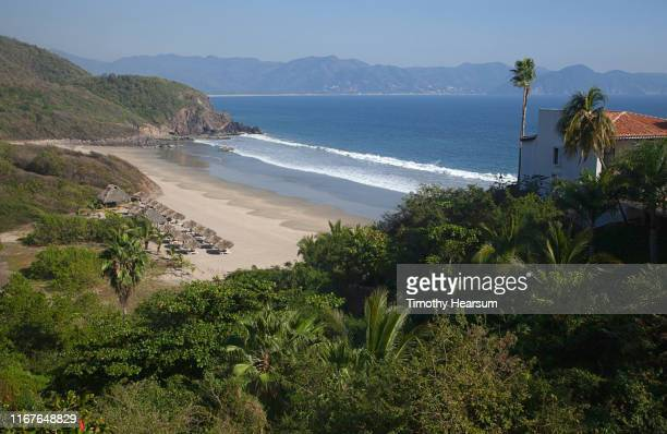 view from above of palapas on a beach at tenacatita bay, costalegre, jalisco, mexico - timothy hearsum stock photos and pictures