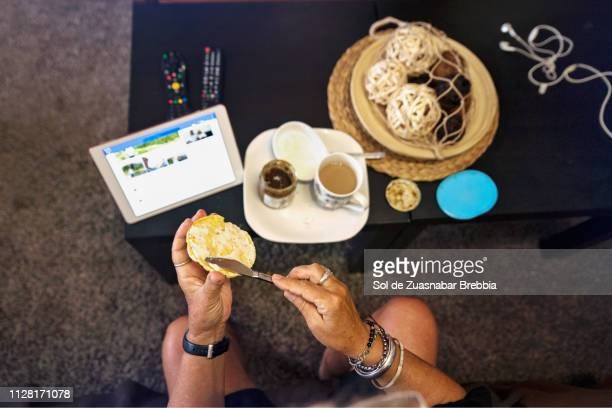 View from above of the hands of a senior woman taking breakfast in the living room and using her digital tablet