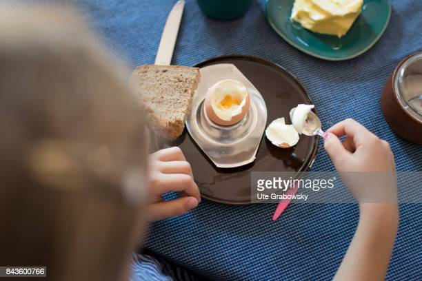 View from above on a fiveyearold girl who is eating a boiled egg on August 07 2017 in Bonn Germany