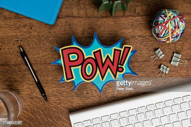 view from above pow sign on wooden desk - comic book stock pictures, royalty-free photos & images