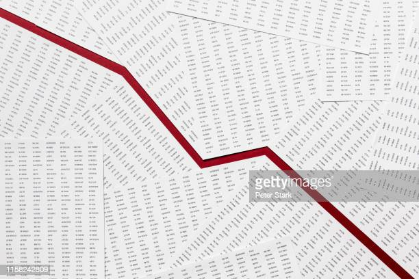 view from above red descending line through paperwork - recession stock pictures, royalty-free photos & images
