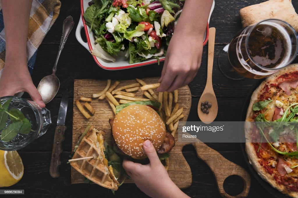 View from above the table of friends eating : Stock Photo