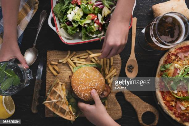view from above the table of friends eating - harvest table stock pictures, royalty-free photos & images