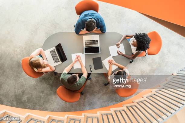 View from above towards five business people around meeting table