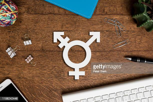 view from above transgender symbol on wooden desk - social justice concept stock pictures, royalty-free photos & images
