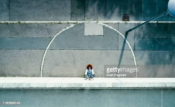 view from above young man meditating on urban sidewalk - gleichgewicht stock-fotos und bilder