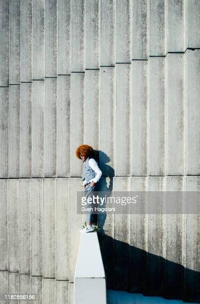 view from above young man with afro laying on sunny urban steps - unusual angle stock pictures, royalty-free photos & images