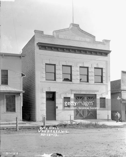 View from across street of the Village Hall/Fire Station Waunakee Wisconsin 1913 There are hitching posts along the curb On the right a young boy...