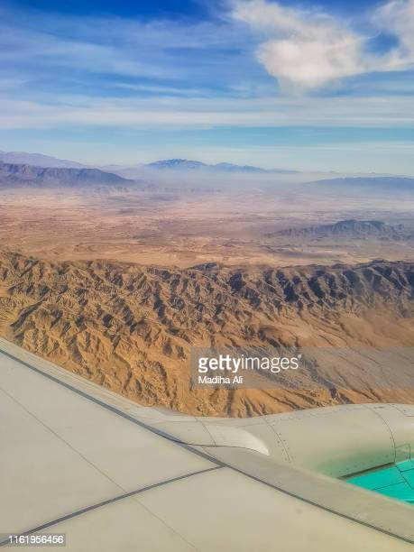 view from an aeroplane window | flying | desert | barren | aircraft wing | cloudy sky - scenics stock pictures, royalty-free photos & images