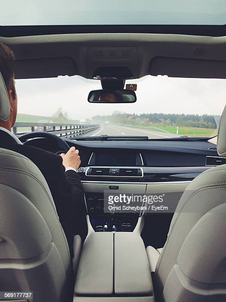 View from back seat of man driving car