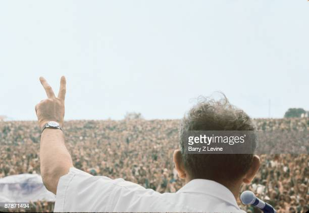 View from behind American farmer Max Yasgur as he addresses the massive crowd with a 'peace sign' from stage during the Woodstock Music and Arts Fair...