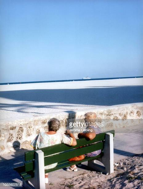 View from behind as a pair of unidentified women sit on a bench and look across the sand towards the ocean in the South Beach neighborhood Miami...