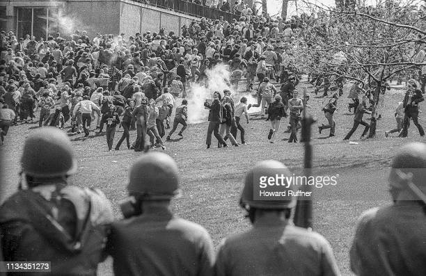View from behind as Ohio National Guardsmen in gas masks and with rifles as they prepare to advance up Blanket Hill through clouds of teargas to...