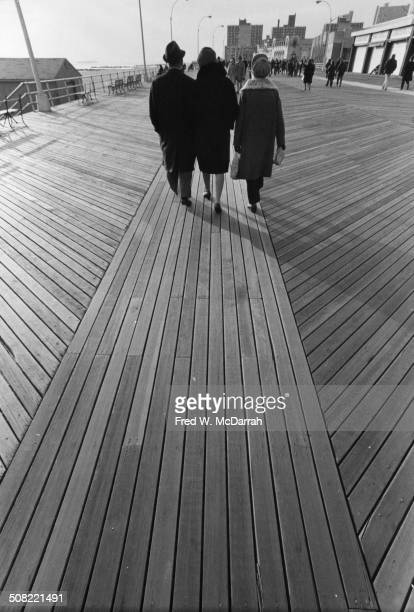 View from behind as three people stroll on the boardwalk at Coney Island New York New York December 3 1972