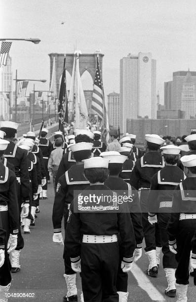 View from behind as uniformed sailors cross the Brooklyn Bridge during its 100th birthday celebrations in Brooklyn New York New York May 24 1983
