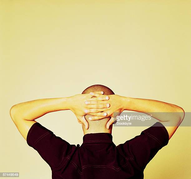 view from behind of a bald man with hands folded behind the head