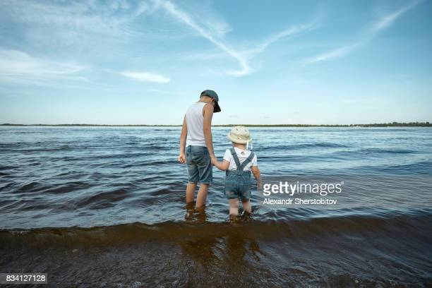 View from behind of a children holding hands, sunny day beneath blue sky scattered with swirling white clouds. Childhood. Travel with kids. Family vacation.