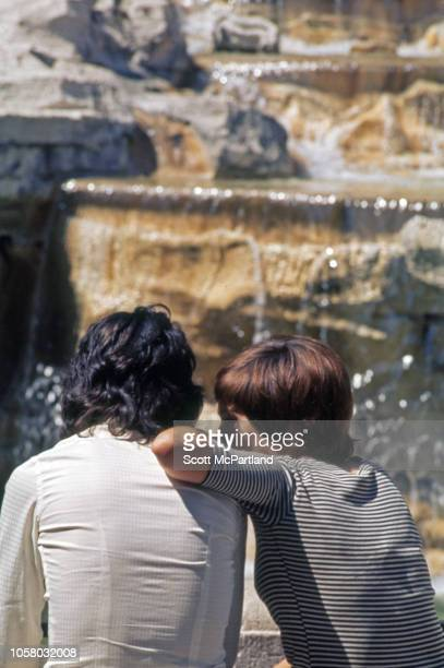 View from behind of a couple as they sit side by side in front of the Trevi Fountain Rome Italy August 1968