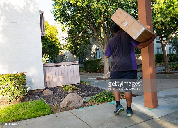 View from behind of a Fedex delivery person carrying a large cardboard box on his shoulder while making a delivery to an apartment complex in Walnut...