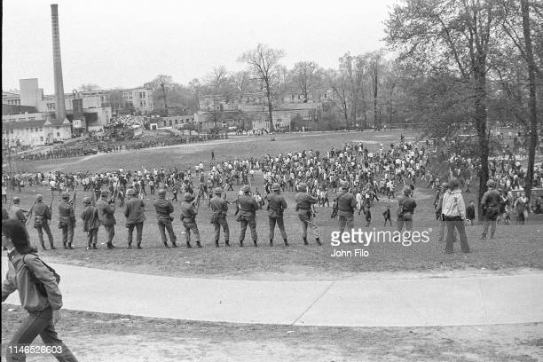 View, from behind, of a line of armed Ohio National Guardsmen as they stand at the top of Blanket Hill, facing the Commons which is full of students,...