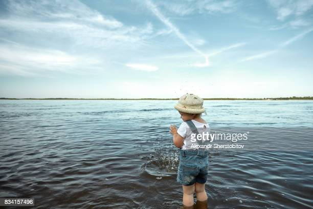 View from behind of a little girl dropping stones to river, sunny day beneath blue sky scattered with swirling white clouds. Childhood. Family vacation.