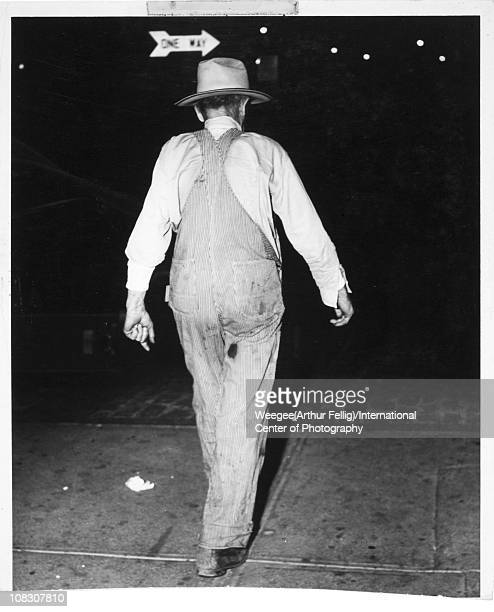 View, from behind, of a man dressed in overalls and wearing a hat, walking along a dark city street, New York, ca 1945. A One Way sign is visible...