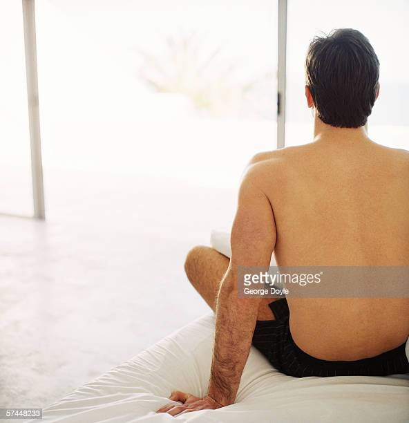 view from behind of a man in shorts sitting on a bed and looking out the window - mid adult men stock pictures, royalty-free photos & images