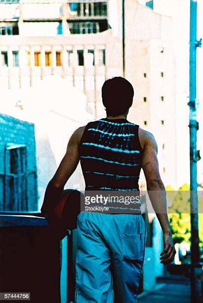 view from behind of a man walking away with a basketball