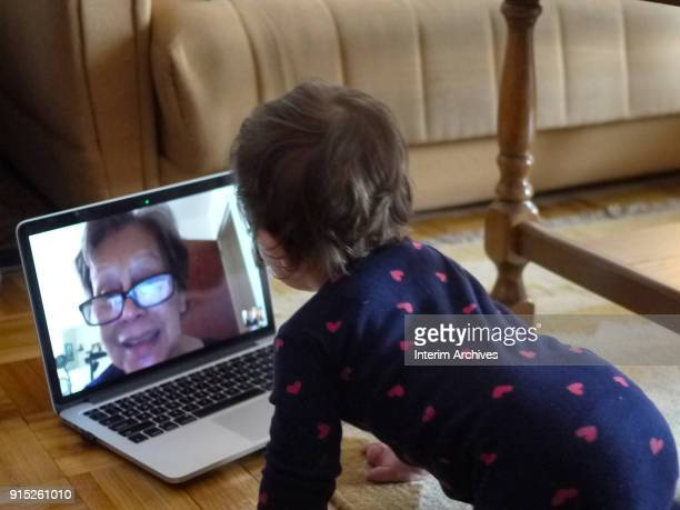 View from behind of a toddler who has a video chat via a laptop computer with an unidentified relative April 6 2015