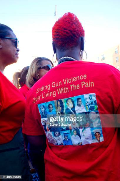 View, from behind, of a woman in a red t-shirt that reads 'Ending Gun Violence, Over Living With the Pain,' during a rally sponsored by St Sabina...