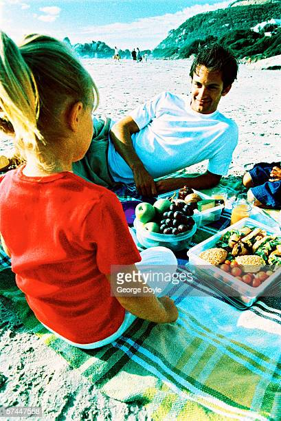 view from behind of a young girl on a beach picnic with her father