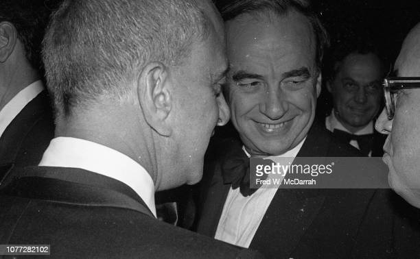 View from behind of American attorney Roy Cohn as he stands with Australianborn American media executive Rupert Murdoch and an unidentified man...