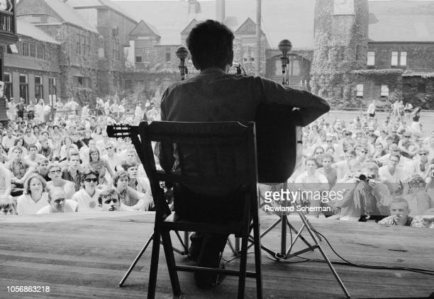 View from behind of American musician Bob Dylan as he plays acoustic guitar during a performance at the Newport Folk Festival Newport Rhode Island...
