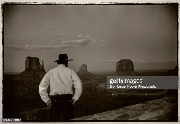 View, from behind, of an unidentified man, hands on his hips, as he looks out towards Monument Valley, New Mexico, 1995.