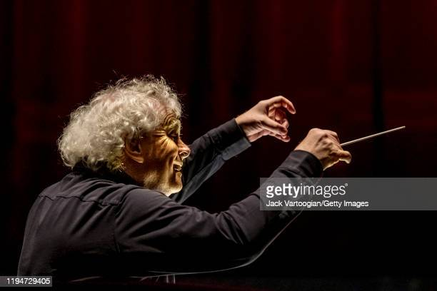 View, from behind, of British conductor Sir Simon Rattle during the final dress rehearsal prior to the season revival of the Metropolitan...