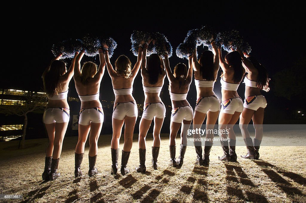 View from behind of Cheerleaders cheering with pompoms in air : Stock Photo