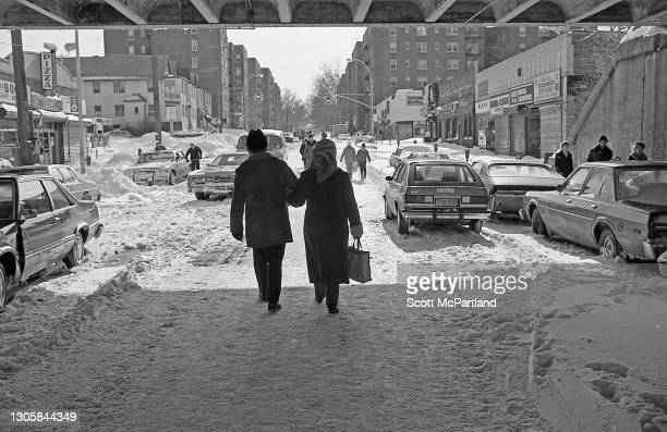 View, from behind, of couple walking arm in arm under a Long Island Rail Road trestle, along the middle of 63rd Drive , in the aftermath of a...
