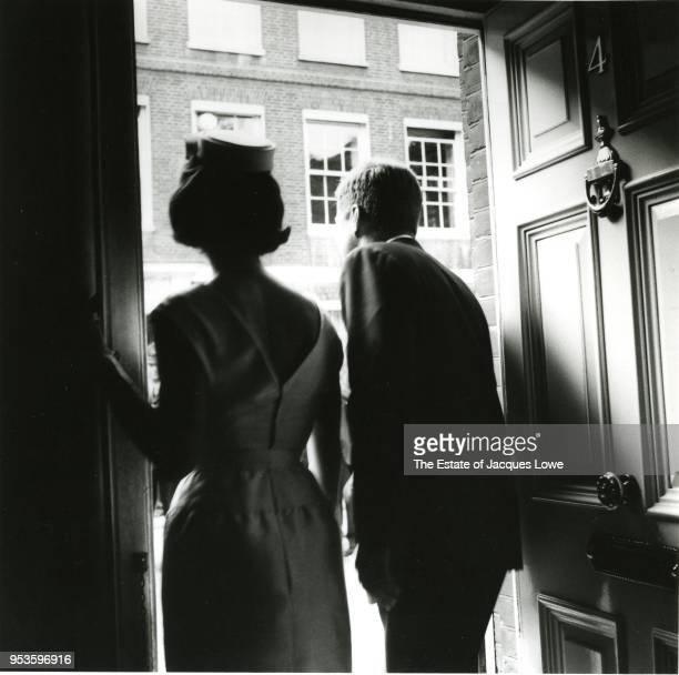 View from behind of married American couple First Lady Jacqueline Kennedy and US President John F Kennedy as they peer through an open door to the...