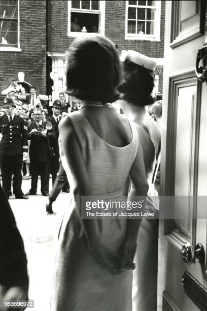 View from behind of married American sisters Princess Lee Radziwill and US First Lady Jacqueline Kennedy as they peer through an open door to the...