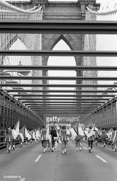 View from behind of members of a marching band as they cross the Brooklyn Bridge during its 100th birthday celebrations in Brooklyn New York New York...
