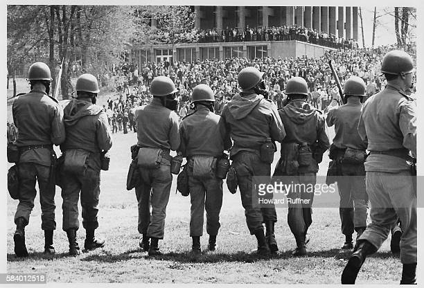 View from behind of members of the Ohio National Guard with gas masks and fixed bayonettes as they advance towards Blanket Hill to disperse antiwar...