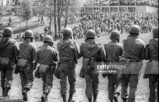 View from behind of Ohio National Guardsmen in gas masks and with rifles as they advance up Blanket Hill to back Kent State University students...