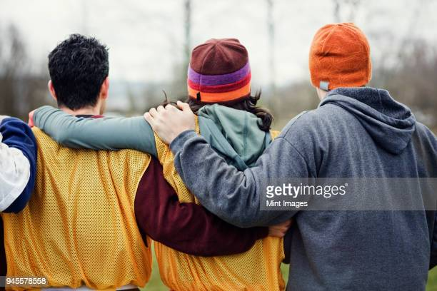 view from behind of three friends with their arms around one another in sports kit and woolly hats. - team sport stock pictures, royalty-free photos & images